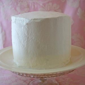 Перемазываем бисквитный корж любимым кремом. Можно приготовить и любые другие коржи. Для большего вкуса я добавила еще и ягоды.  Кладем наверх второй корж. Опять перемазываем.  Я готовила высокий торт, поэтому мне понадобилось 3 коржа.  Шпателем наносим айсинг на торт, аккуратно покрываем и разравниваем со всех сторон.  Низ и верх украшаем широкими завитушками из крема, воспользовавшись кондитерским мешком с широкой насадкой.  Наносим сухой кисточкой кандурин на крем, просто легко встряхивая. Разводим кандурин в небольшом количестве водки (буквально чуть-чуть) и окрашиваем поверхность торта. Можно кисточкой, но удобнее это делать с помощью распылителя. В завершение я для большего эффекта украсила торт канделябром со свечами и ягодами.  А вот так десерт выглядит на разрезе.  Согласитесь, увидев такой торт, никто не догадается и не поверит, насколько просто он был украшен! Замечательный десерт к юбилеям и праздникам. Готовьте с удовольствием! -шаг 4