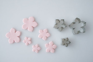 Все инструменты для изготовления можно приобрести в кондитерском магазине.  Окрашиваем мастику в розовый цвет, раскатываем скалкой и вырезаем из нее заготовки формочкой.  Или используем для изготовления молд (как пользоваться молдами, я рассказывала подробно раньше).  Если вы вырезаете формочками, то понадобится нанести на лепестки прожилки (стеком или зубочисткой). Немного выгибаем лепестки и припудриваем пищевой пудрой.  В серединки фиалок приклеиваем пищевые бусинки, оставляем сохнуть.  Украшаем цветами кондитерское изделие. Просто, но очень изящно! Удачи, у вас все получится!-шаг 2