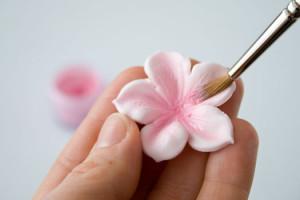 Все инструменты для изготовления можно приобрести в кондитерском магазине.  Окрашиваем мастику в розовый цвет, раскатываем скалкой и вырезаем из нее заготовки формочкой.  Или используем для изготовления молд (как пользоваться молдами, я рассказывала подробно раньше).  Если вы вырезаете формочками, то понадобится нанести на лепестки прожилки (стеком или зубочисткой). Немного выгибаем лепестки и припудриваем пищевой пудрой.  В серединки фиалок приклеиваем пищевые бусинки, оставляем сохнуть.  Украшаем цветами кондитерское изделие. Просто, но очень изящно! Удачи, у вас все получится!-шаг 4