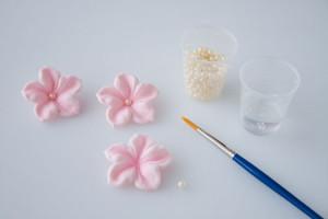 Все инструменты для изготовления можно приобрести в кондитерском магазине.  Окрашиваем мастику в розовый цвет, раскатываем скалкой и вырезаем из нее заготовки формочкой.  Или используем для изготовления молд (как пользоваться молдами, я рассказывала подробно раньше).  Если вы вырезаете формочками, то понадобится нанести на лепестки прожилки (стеком или зубочисткой). Немного выгибаем лепестки и припудриваем пищевой пудрой.  В серединки фиалок приклеиваем пищевые бусинки, оставляем сохнуть.  Украшаем цветами кондитерское изделие. Просто, но очень изящно! Удачи, у вас все получится!-шаг 5