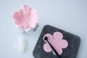 Стакан накрываем фольгой, сделав углубление.  Окрашиваем мастику в розовый цвет. Раскатываем. Делаем низ цветка с пятью лепестками. Можно нарисовать шаблон и вырезать затем из мастики. Или воспользоваться вайнером, формочкой. Стеком разравниваем лепестки. Помещаем заготовку на стакан.  Из белой мастики делаем точно такую же заготовку, но меньшего размера.  Наносим клей на заготовку с розовыми лепестками.  Приклеиваем заготовку с белыми лепестками. Оставляем сохнуть.  Так повторяем несколько слоев, каждый раз делая заготовки меньшего размера.   Чем больше слоев, тем красивее получается цветок.  Сделайте сердцевину цветка, припудрите белой пудрой.   Приклейте посередине.  Изготовьте тоненькие тычинки. Когда они высохнут, приклейте их к серединке с помощью пинцета.  Последний штрих – украшаем серединку розовой пудрой.  Оставляем сохнуть цветок в стакане на 1-2 дня, украшаем торт. Смотрится такое украшение очень красиво, цветок необычный и нежный. И, согласитесь, делается очень просто!-шаг 2