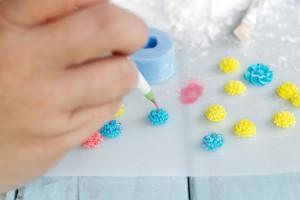 Окрашиваем мастику в различные цвета. На рабочую поверхность высыпаем сахарную пудру, берем вайнеры. Присыпаем немного отверстия сахарной пудрой. Стряхиваем лишнее. Берем мастику, например, желтого цвета. Отщипываем по небольшому кусочку. Разминаем. Наполняем мастикой вайнеры. Получаются вот такие разные заготовки (можно использовать различные). После высыхания аккуратно вынимаем. Ставим точечки фломастерами. Получаются вот такие красивые цветочки.  Посмотрите, как они выглядят восхитительно, если ими украсить торт! Настоящая «цветочная клумба»!-шаг 3
