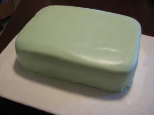 Тщательно разминаем мастику.  Изготавливаем вот такие детали для чемодана.  Раскрашиваем пищевыми красками.  Покрываем торт мастикой.  Делаем ободок, приклеиваем ручки.  Добавляем другие детали.  Получается весьма оригинальный торт из мастики! Кстати, украшать его можно, как угодно, например, создав аналог своего любимого чемодана. -шаг 3