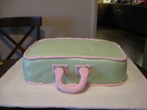 Тщательно разминаем мастику.  Изготавливаем вот такие детали для чемодана.  Раскрашиваем пищевыми красками.  Покрываем торт мастикой.  Делаем ободок, приклеиваем ручки.  Добавляем другие детали.  Получается весьма оригинальный торт из мастики! Кстати, украшать его можно, как угодно, например, создав аналог своего любимого чемодана. -шаг 4