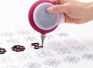 Нарисуйте на пергаментной бумаге любые фигурки. Возьмите трафарет и прикройте сверху пергаментной бумагой. Растопите шоколад в микроволновке или на водяной бане. Тщательно перемешайте, чтобы не оставались комочки. Теплый шоколад перелейте в кондитерский мешок или другое приспособление. Аккуратно обведите контуры будущих фигурок. Отправьте в холодильник до полного застывания. Аккуратно отделите фигурки от бумаги. Украсьте десерт.  Все гениальное – просто. И вы сейчас сами в этом убедились! Оставайтесь с нами, подписывайтесь на наш сайт, вас ждет немало интересного. С нами вы станете настоящими кондитерами! -шаг 3