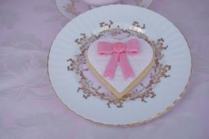 Привожу вам пример на печенье. Испеките, например, бисквитное печенье оригинальной формы: сердечками, цветочками и так далее.  Раскатайте тонко мастику. Можно ее окрасить, но лучше оставить белого цвета, так на ней эффектнее смотрятся другие украшения.  Нанесите узор ажурным ковриком, придавив к мастике. Затем вырежьте формочками заготовки (в этом случае сердечки). Покройте мастикой печенье.  Окрасьте мастику в выбранный вами цвет, сделайте бантик. Как делать бант из мастики, я описывала раньше подробно в мастер-классе.  Возьмите молд «ассорти». Обычно такие молды продаются в кондитерских магазинах в огромном ассортименте, так что есть из чего выбрать. Очень удобные в использовании и не раз выручают в работе. С помощью такого молда сделайте украшение для банта. Приклейте бант на мастику пищевым клеем (можно заменить взбитым белком).  Все элементарно, все просто! А насколько выглядит красиво! Удачи вам, до новых встреч и идей!-шаг 1